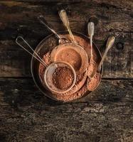 Schokoladenpulver in Metallplatte mit Löffeln auf dunklem Holz foto