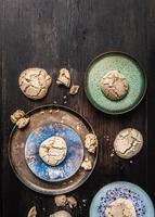 Kekse mit Rissen in emaillierten Schalen auf dunklem Holztisch