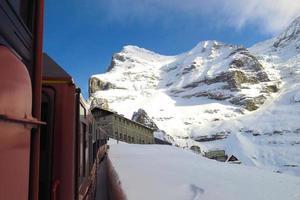 Zug zum Jungfraujoch durch schneebedeckte Schweizer Alpen Winter foto