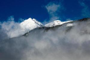 schneebedeckter Berg, der über Wolken mit blauem Himmel aufsteigt