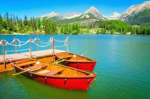 rote Holzboote auf Bergsee in der Slowakei