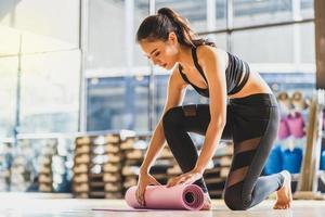 junge asiatische Frau rollende Yogamatte nach dem Üben