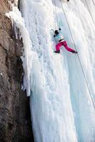 Frau klettert gefrorenen Wasserfall foto