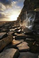 schöner Landschaftsbildwasserfall, der in Felsen am Strand fließt