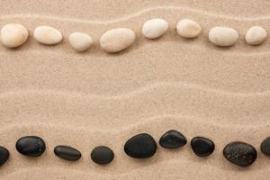 zwei Reihen weißer und schwarzer Steine im Sand