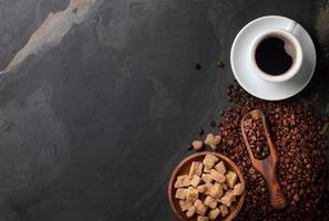 Kaffeetasse, Bohnen und brauner Zucker auf Steintisch foto