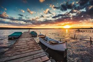 friedlicher Sonnenuntergang mit dramatischem Himmel und Booten und einem Steg