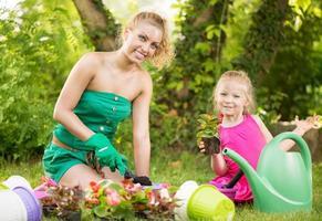 schöne Mutter und Tochter pflanzen Blumen