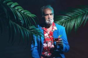 stilvoller älterer Mann mit Cocktail zwischen Pflanzen foto