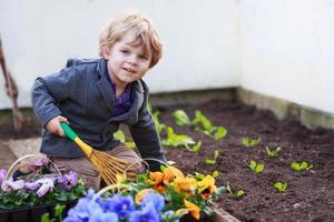 kleiner Junge, der im Garten arbeitet und Blumen pflanzt