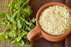 Tasse Reis und Korianderblätter auf einem Tisch foto