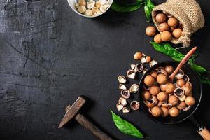 Macadamia-Nüsse auf einem schwarzen hölzernen Hintergrund