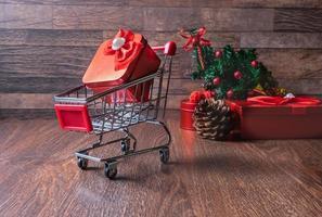 Weihnachtsgeschenke mit einem Miniatur-Einkaufswagen foto