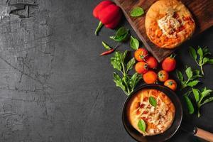 Pizza in der Pfanne und auf Holztablett