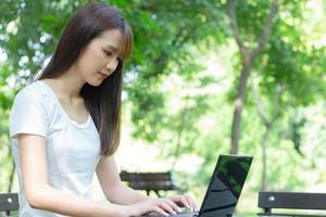 asiatische Frau, die mit einem Laptop in einem Park sitzt