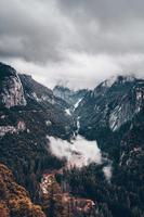 bewölkter Himmel über bergigem Gelände und Wald