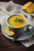 Kürbissuppe mit Petersilie auf Vintage Tisch foto