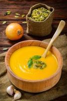 hausgemachter rustikaler Holztisch der Butternusskürbissuppe im Herbst foto