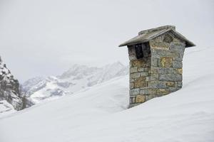 Berghausdach mit rauchendem Schornstein foto