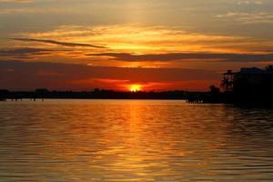Haus auf dem Wasser während des Sonnenuntergangs foto