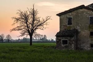 altes Haus mit Baum bei Sonnenuntergang