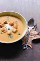 serviert hausgemachte Kürbissuppe