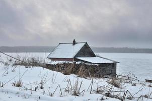 rustikales Haus in der Nähe des Sees im Winter foto