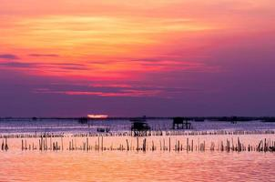 Silhouette des thailändischen Fischerhauses bei Sonnenuntergang foto