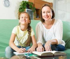 Mutter mit Tochter machen Hausaufgaben