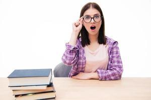 überraschte Frau, die mit Büchern am Tisch sitzt