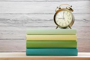 Stapel bunte Bücher und Wecker auf Holztisch.