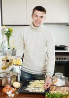 schöner Mann, der rohen Fisch mit Zitrone kocht