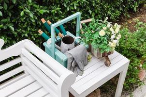 Gartengeräte auf weißem Holztisch und Bank