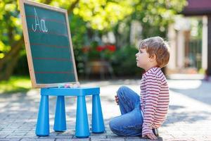 kleiner Junge an der Tafel, der Mathematik übt foto