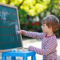 kleiner Junge an der Tafel, der Mathematik übt