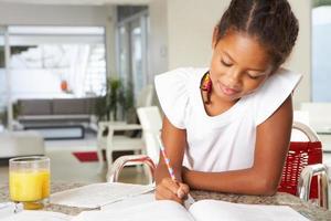 junges Mädchen glücklich, ihre Hausaufgaben in der Küche zu machen