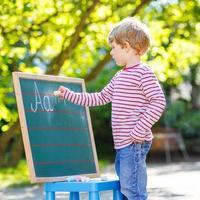 kleiner Junge an der Tafel lernt schreiben foto