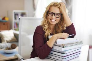 hübsche Studentin, die sich auf einen Stapel Buch stützt