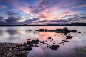Rock, Algen und Boje im Vordergrund mit dramatischem Sonnenuntergangshimmel