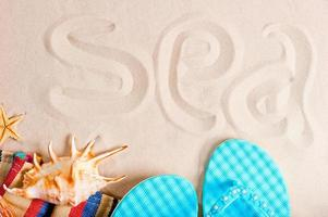 Meeresinschrift auf dem feinen Sand und Strandutensilien foto