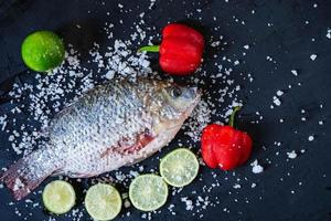 frischer Tilapia-Fisch mit Salz und Gewürzen foto