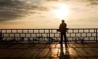 Schattenbild eines Mannes über schönem Sonnenunterganghintergrund
