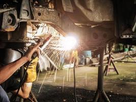 Schweißer repariert hängendes Auto