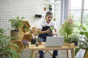 asiatischer Mann, der mit Zimmerpflanzen arbeitet foto