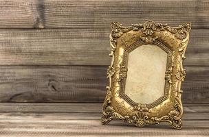 goldener barocker Bilderrahmen auf hölzernem Hintergrund