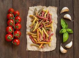 dreifarbige Nudeln mit Kirschtomaten, Knoblauch und Basilikum foto