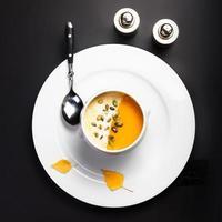 Kürbissuppe mit Sahne und Samen in weißer Schüssel