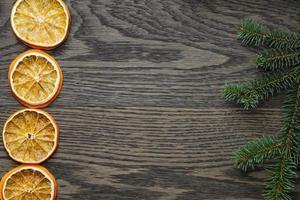 Fichtenzweig mit getrockneten Orangenscheiben auf Eichentisch foto