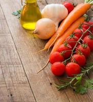 Bio-Gemüse und Olivenöl auf einem Holztisch foto