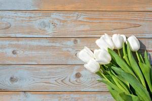 Bündel weißer Tulpen mit leerem Raum auf altem Holz foto